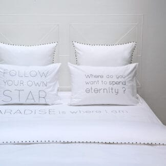 Hand-embroidered quotes on white bed linen with black thread