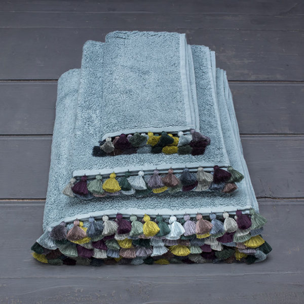 water color bath linen with colored pompoms folded