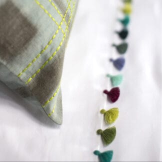 Bed linen with multicolor pompoms in casapiedra color,