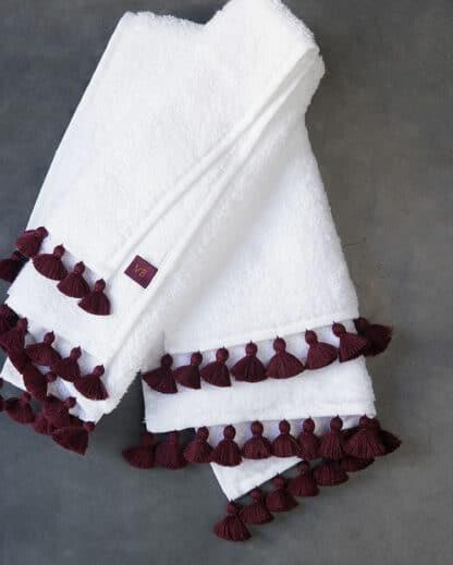 white bath linen with plum pompoms
